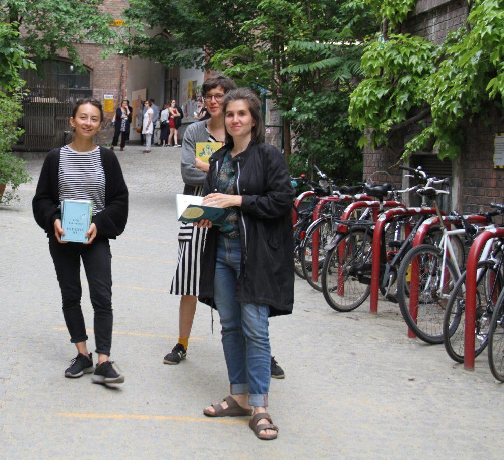 Drei junge Frauen mit Büchern stehen im WuK-Hof: Kathi Pech, Greta Egle und Sara Schausberger