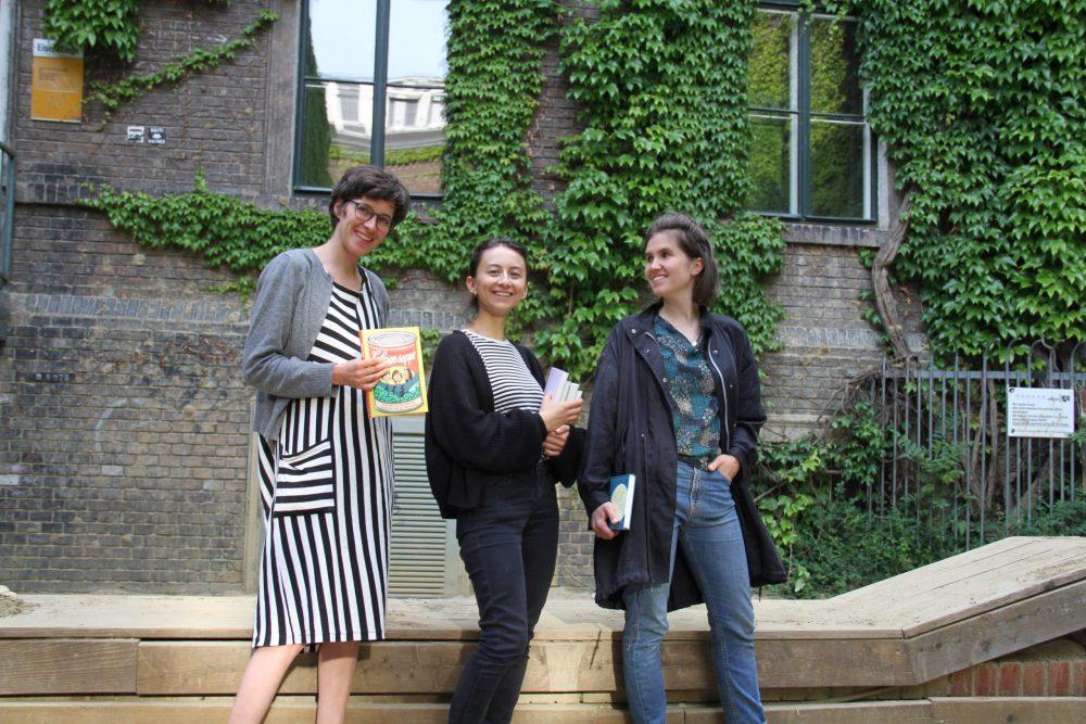 Drei junge Frauen mit Büchern stehen vor einer Holzumrandung der Sandksite und einer begrünten Wand im WuK-Hof: Greta Egle, Kathi Pech und Sara Schausberger