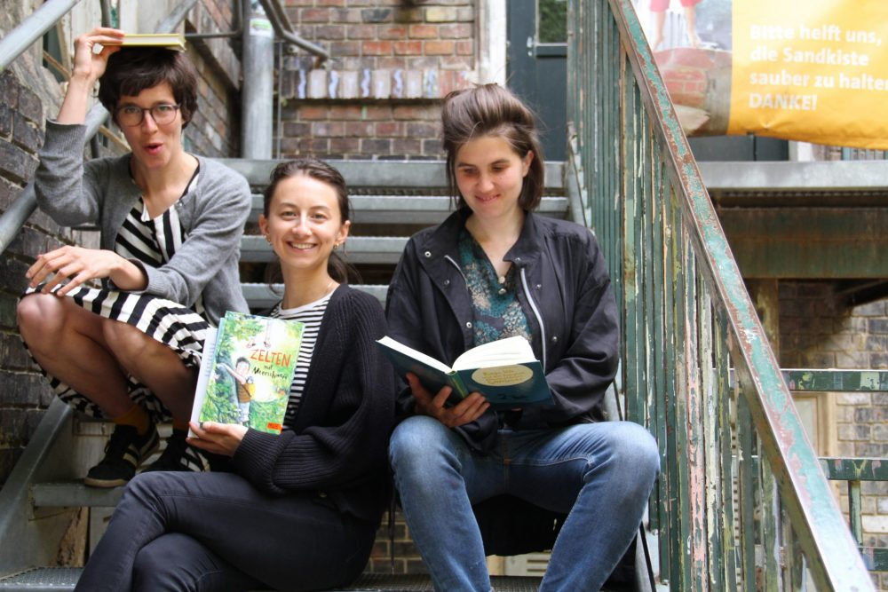 Drei junge Frauen mit Büchern sitzen auf einer Metall-Stiege im WuK-Hof: Greta Egle, Kathi Pech und Sara Schausberger