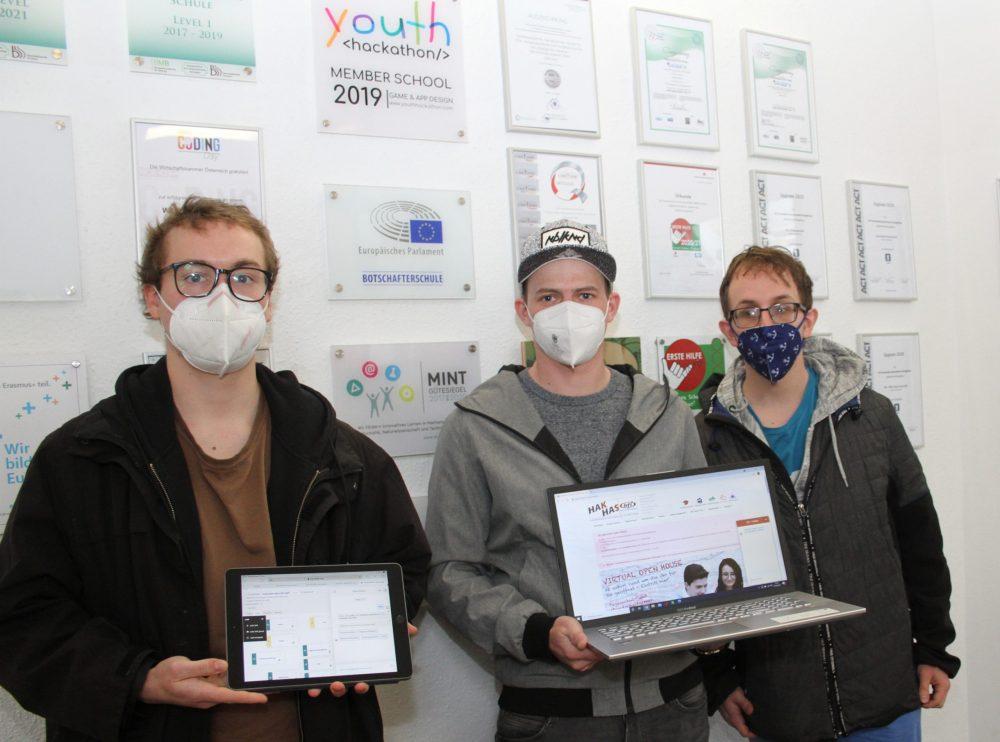 Drei Schüler mit Tablet und Laptop vor der Schulwand mit Auszeichnungen