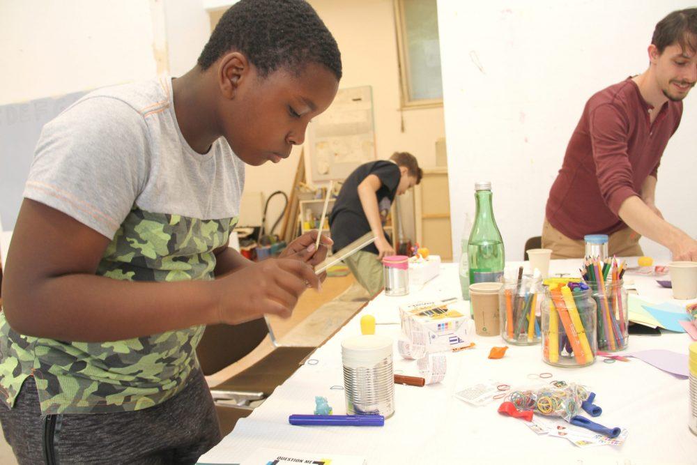 Kinder bauen aus einer leeren, offenen Konsreendose und einem aufgeschnittenen Luftallon eine Trommel