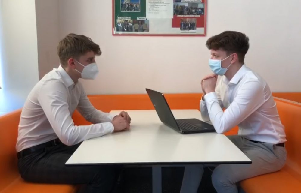 Zwei Jugendliche sitzen einander gegenüber, einer mit Laptop, beide mit FFP2-Masken