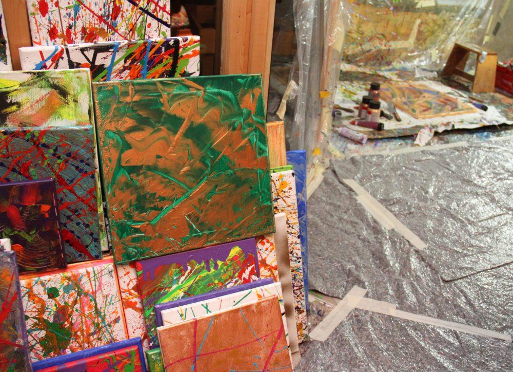 Viele gemalte bilder stehen am Boden und lehnen an der Wand