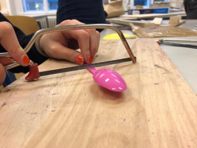 Hände, die Kunststoffteile sägen
