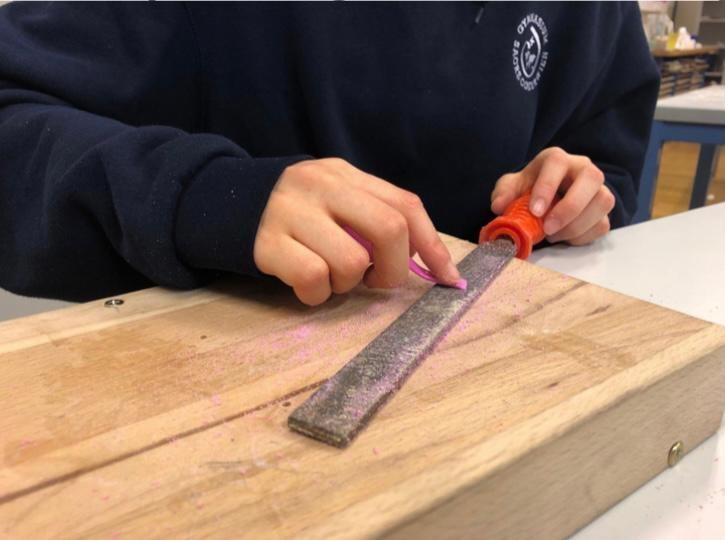 Hände, die kleine Kunststoffteile schleifen
