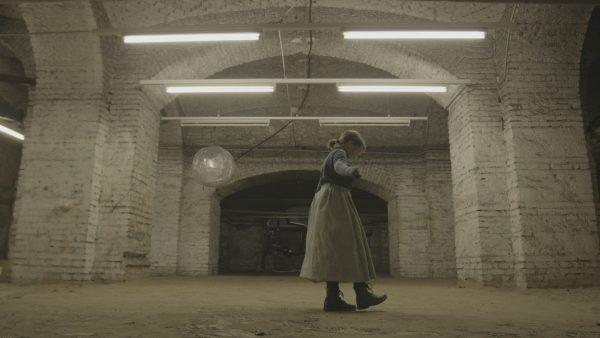 Jugendliche Schauspielerin setzt einen Fuß vor den anderen in den Sand im Keller