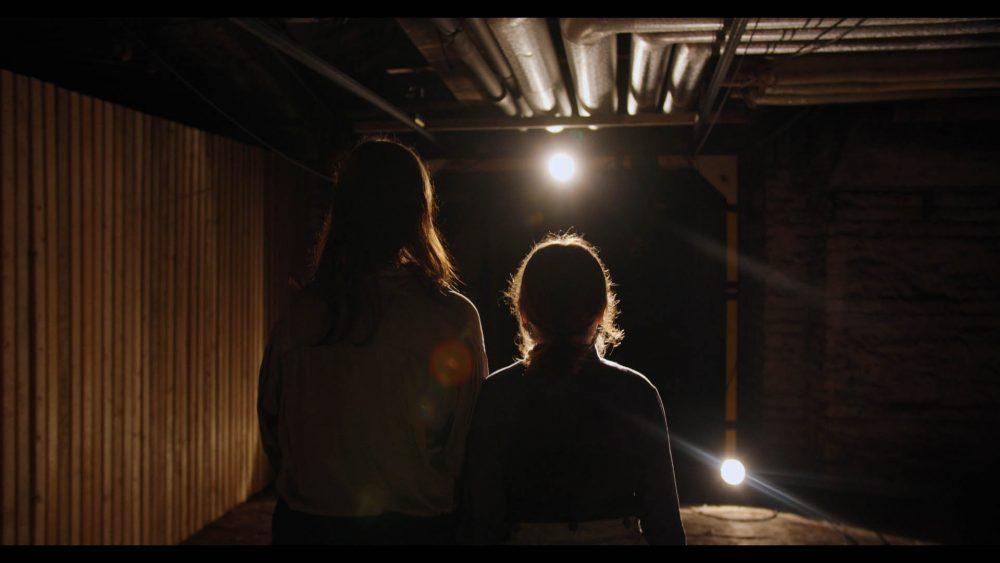 Mutter und Tochter - von hinten gesehen - gehen in einem Kellergang