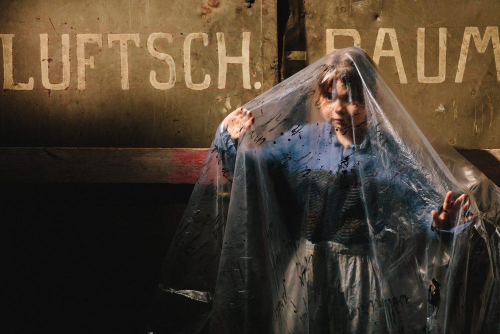 Jugendliche Schauspielerin mit durchsichtiger mit Text bedruckter Folie