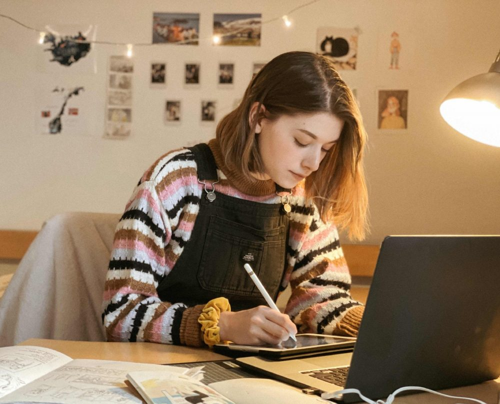 Die Illustratorin mit ihrem Zeichen-Tablet vor dem Laptop
