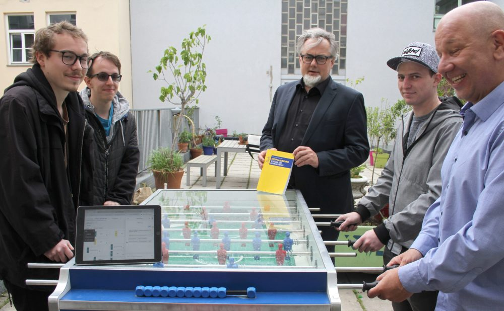 Schüler und Lehrer spielen Tischfußball, ein Laptop mit der Schulhomepage und der Direktor mit Buch zur Digitalisierung